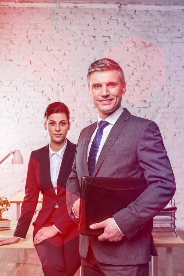 Retrato de los colegas confiados del negocio que se colocan en la oficina fotografía de archivo libre de regalías