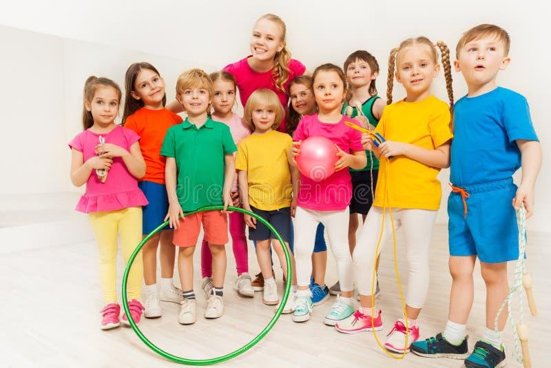 Retrato de los deportes felices profesor y niños en el gimnasio imagenes de archivo