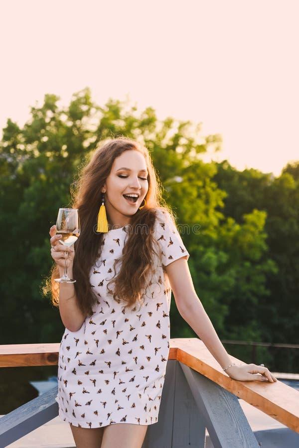 Retrato de los dientes atractivos jovenes hermosos de una sonrisa de la muchacha en un vestido corto blanco del verano en a de la imágenes de archivo libres de regalías