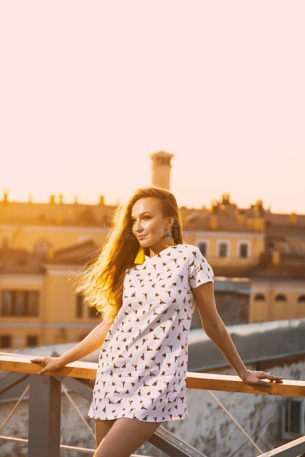 Retrato de los dientes atractivos jovenes hermosos de una sonrisa de la muchacha en un vestido corto blanco del verano en a de la foto de archivo libre de regalías