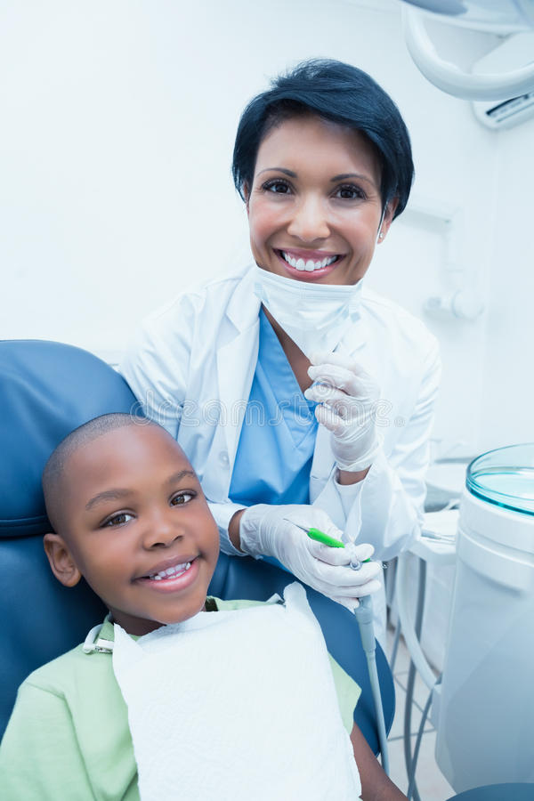 Retrato de los dientes de examen sonrientes de los muchachos del dentista de sexo femenino imagen de archivo
