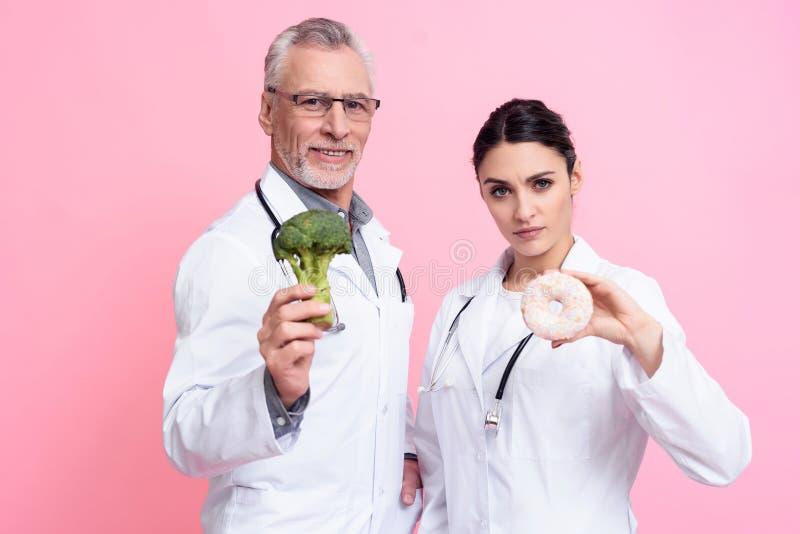 Retrato de los doctores de sexo masculino y de sexo femenino con los estetoscopios que sostienen el bróculi y el buñuelo aislados imagen de archivo