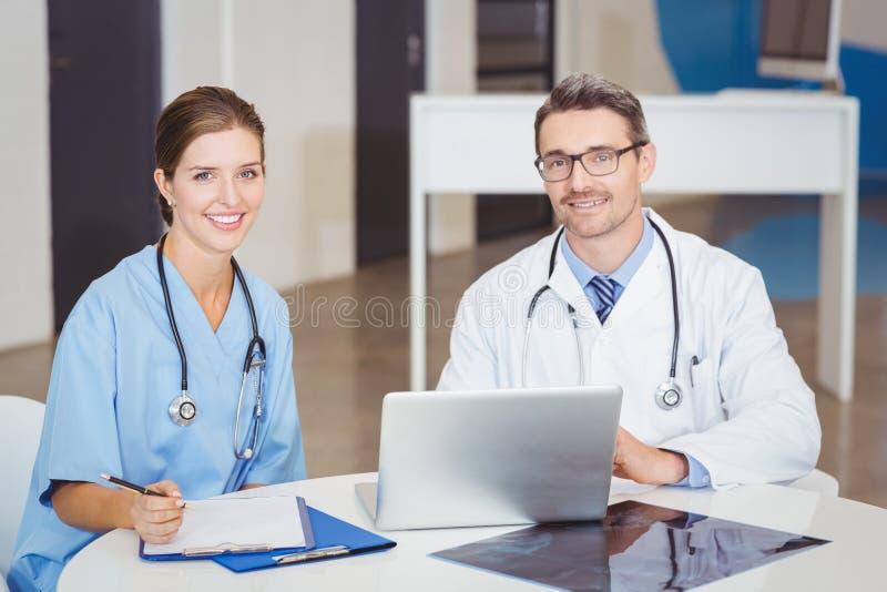 Retrato de los doctores sonrientes que se sientan en el escritorio foto de archivo libre de regalías