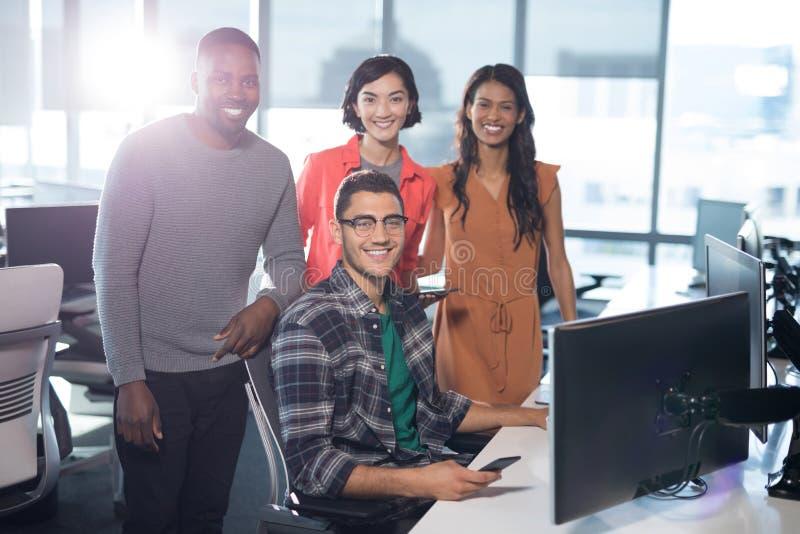 Retrato de los ejecutivos de operaciones que sonríen en el escritorio imagenes de archivo