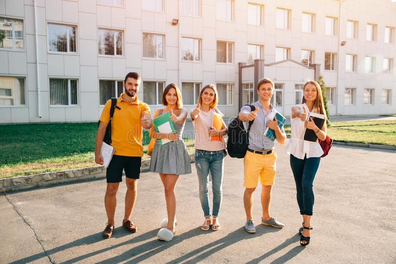 Retrato de los estudiantes del grupo en equipo casual con los libros que muestran los pulgares para arriba fotos de archivo libres de regalías