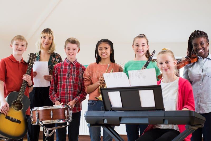 Retrato de los estudiantes de la High School secundaria que juegan en ingenio de la orquesta de la escuela fotos de archivo libres de regalías