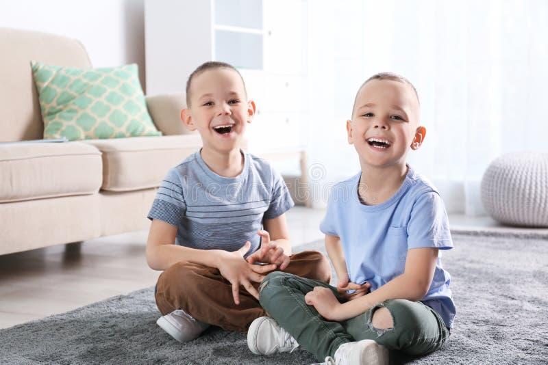 Retrato de los hermanos gemelos lindos que se sientan en piso foto de archivo