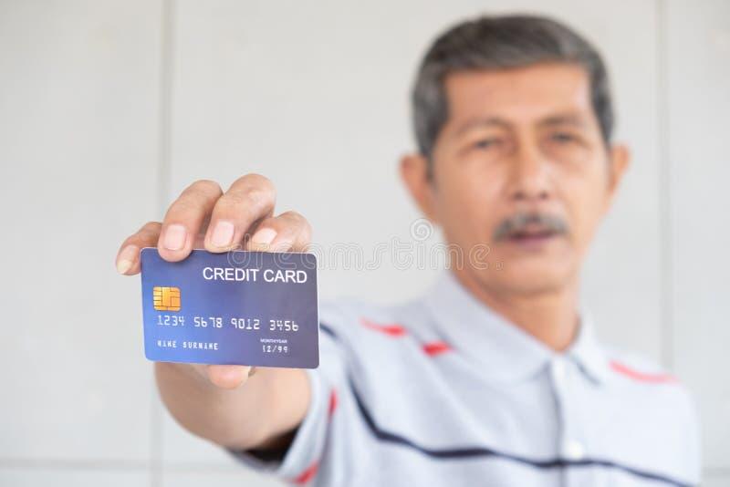 Retrato de los hombres de negocios y de la tarjeta de crédito mayores de la demostración imagenes de archivo