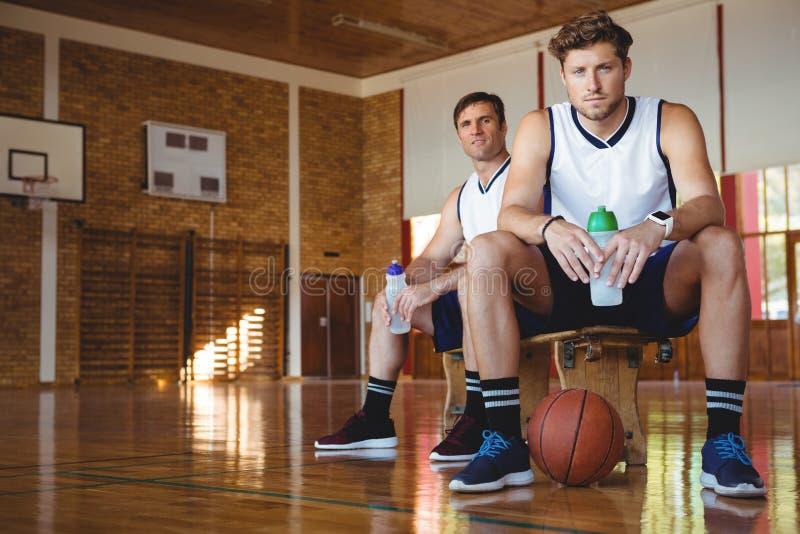 Retrato de los jugadores de básquet confiados que se sientan en banco imagenes de archivo