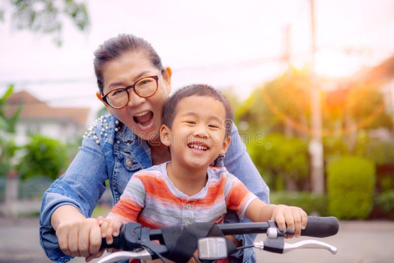 Retrato de los niños asiáticos que montan la bicicleta con la emoción sonriente de la felicidad de la cara de la madre imagen de archivo libre de regalías
