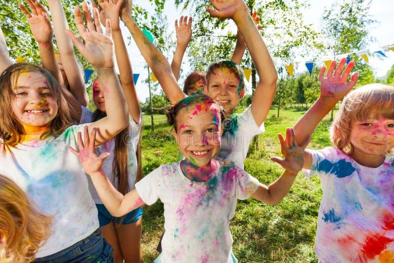 Retrato de los niños brillantes manchados en polvo coloreado fotos de archivo