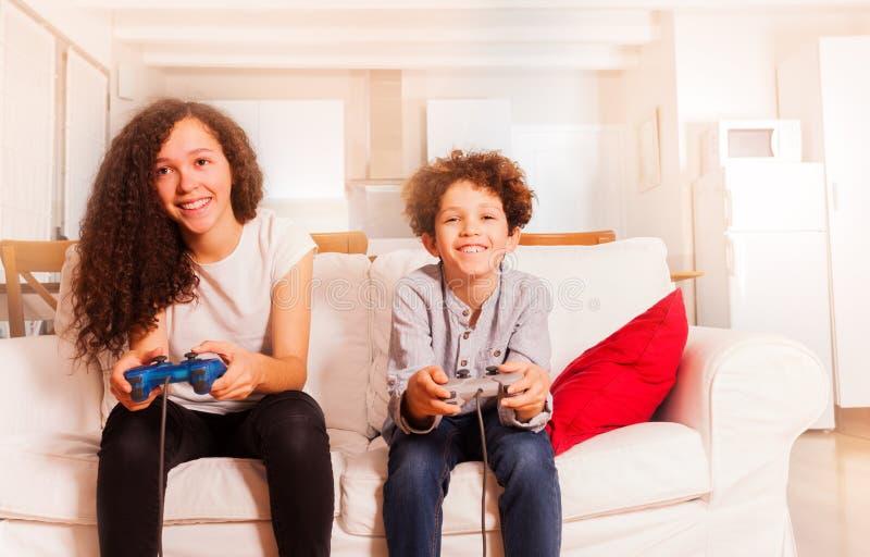 Retrato de los niños felices que juegan a los videojuegos imagen de archivo