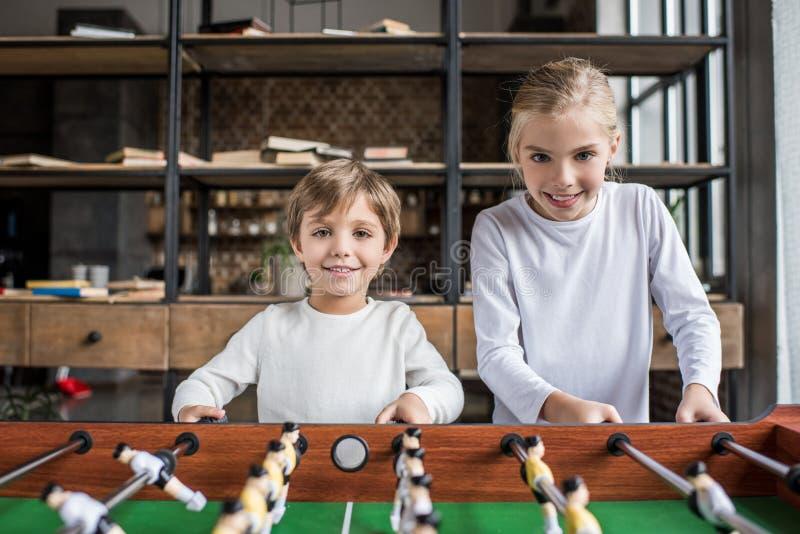 retrato de los niños lindos que juegan al fútbol de la tabla junto fotografía de archivo