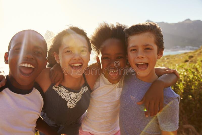 Retrato de los niños sonrientes que defienden en los acantilados el mar fotografía de archivo libre de regalías