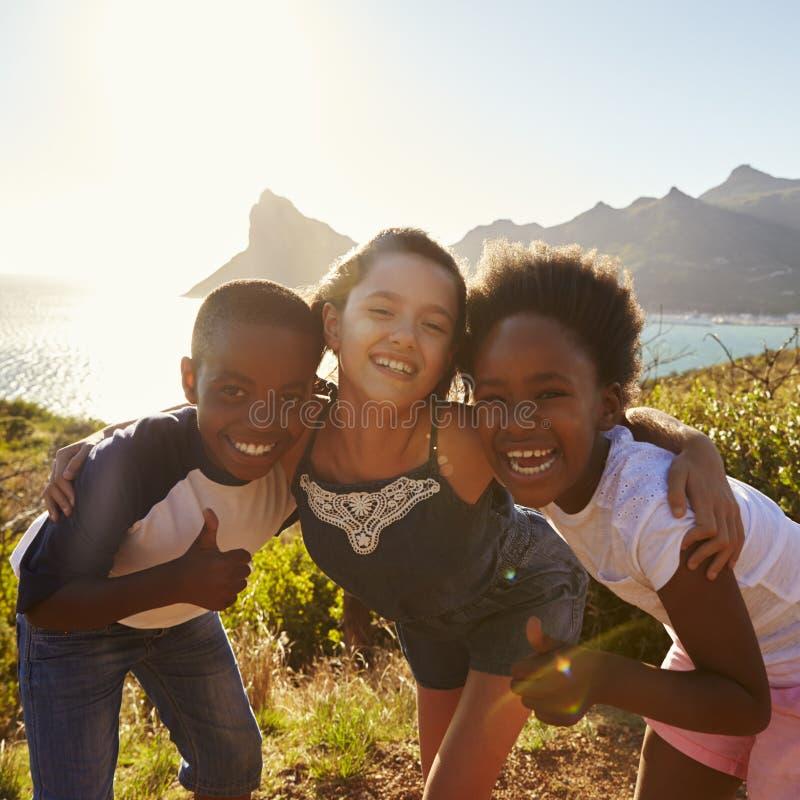 Retrato de los niños sonrientes que defienden en los acantilados el mar foto de archivo