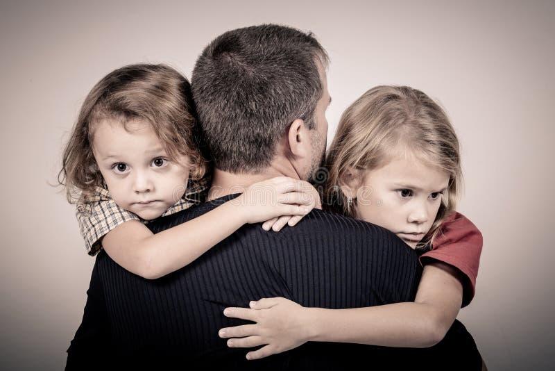 Retrato de los niños tristes uno que abrazan a su padre fotografía de archivo libre de regalías