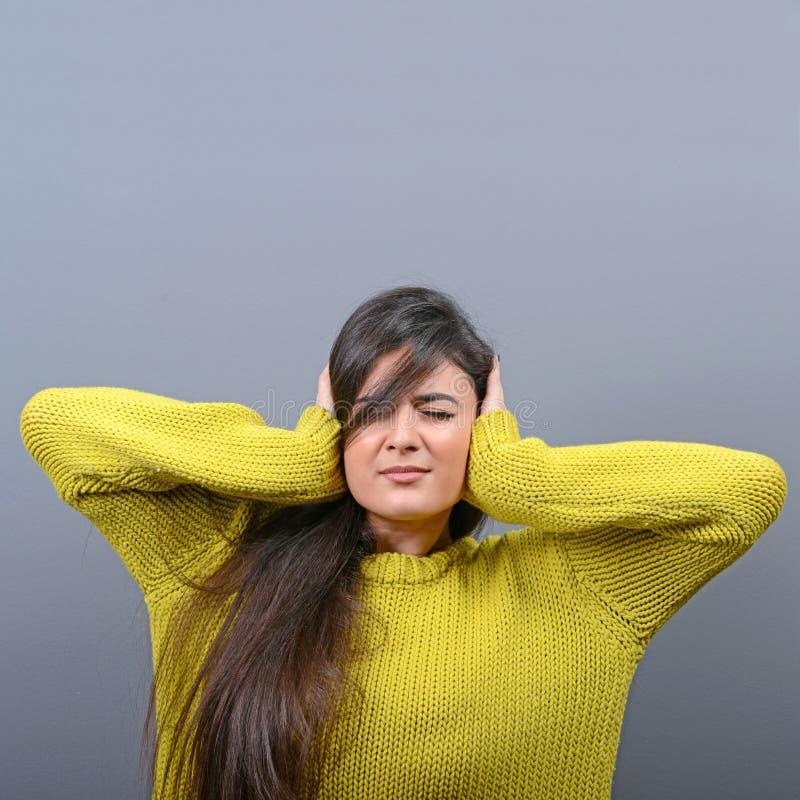 Retrato de los o?dos de la cubierta de la mujer con las manos contra fondo gris foto de archivo