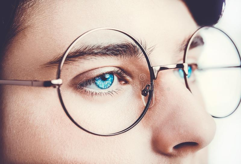 Retrato de los ojos azules de las lentes de un muchacho que llevan cerca, tiro macro del estudio imagen de archivo