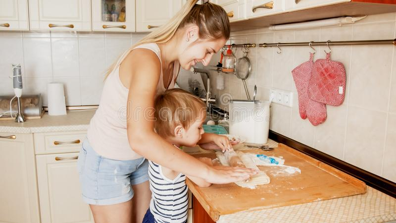 Retrato de los 3 a?os lindos del ni?o peque?o que cocina las galletas con la madre Familia que cocina y que cuece imagen de archivo libre de regalías