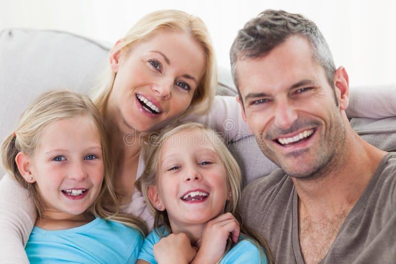 Retrato de los padres y de los gemelos que se sientan en un sofá fotos de archivo