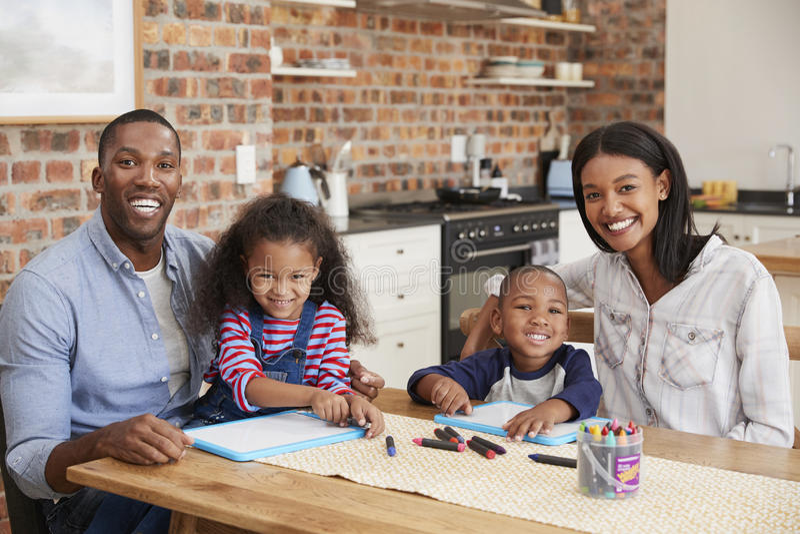 Retrato de los padres y de los niños que dibujan en la tabla foto de archivo