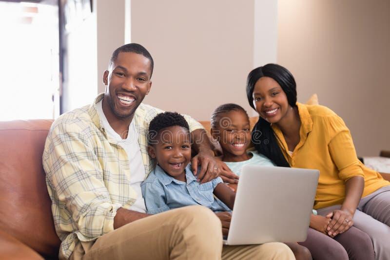Retrato de los padres y de los niños que sostienen el ordenador portátil mientras que se sienta en el sofá fotos de archivo
