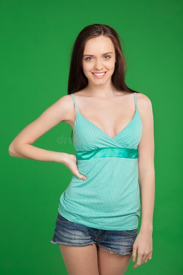 Retrato de los pantalones cortos que llevan sonrientes hermosos de la muchacha triguena encima imagenes de archivo