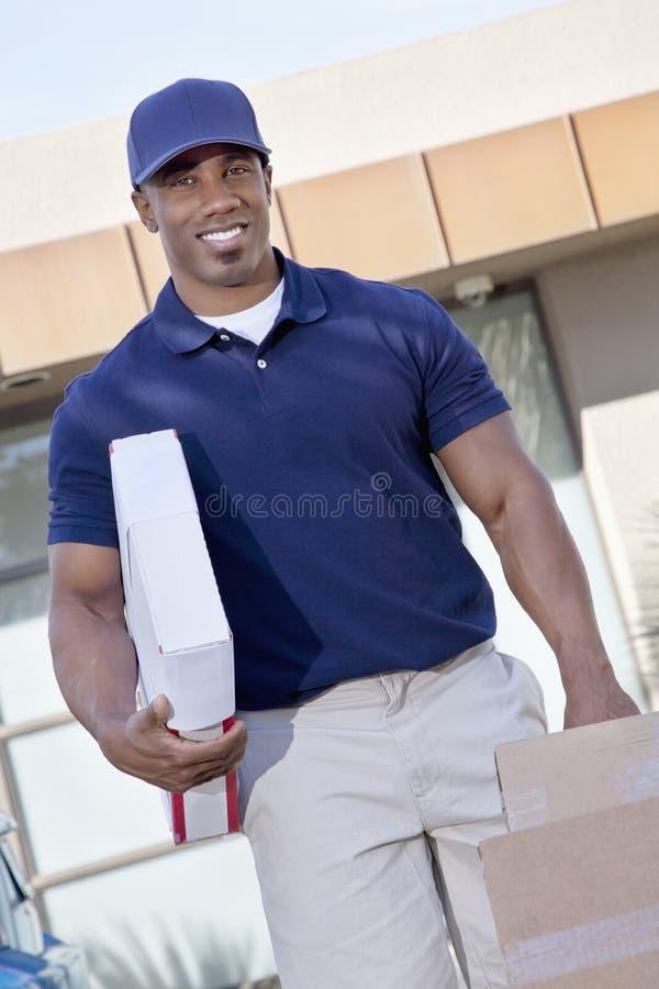Retrato de los paquetes que llevan felices de un hombre de entrega imagen de archivo libre de regalías