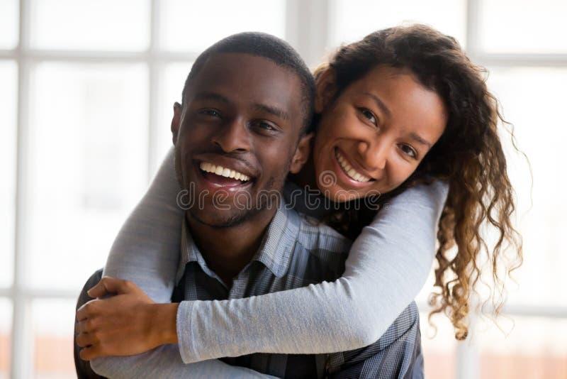 Retrato de los pares afroamericanos felices que abrazan mirando c fotografía de archivo