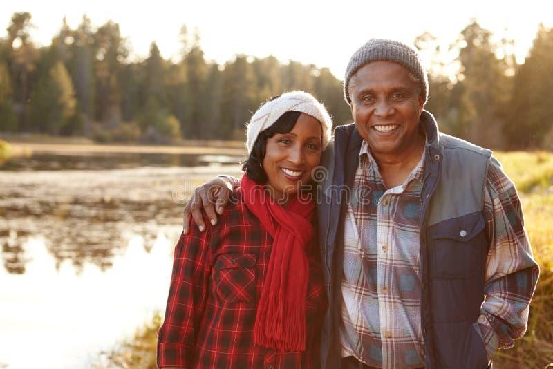 Retrato de los pares afroamericanos mayores que caminan por el lago foto de archivo