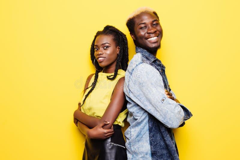 Retrato de los pares afroamericanos que se colocan de nuevo a la parte posterior aislada sobre fondo amarillo fotos de archivo