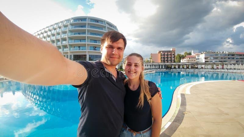 Retrato de los pares alegres felices que hacen el retrato del selfie de smartphone contra piscina en hotel Familia que se relaja fotografía de archivo