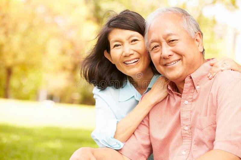 Retrato de los pares asiáticos mayores que se sientan en parque junto foto de archivo