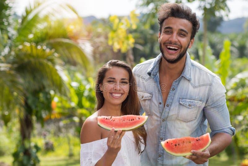 Retrato de los pares felices que comen el hombre alegre y a la mujer de la sandía junto que llevan a cabo la rebanada de sandía a fotografía de archivo libre de regalías