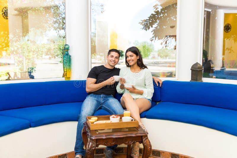 Retrato de los pares felices que desayunan junto en el sofá imagen de archivo