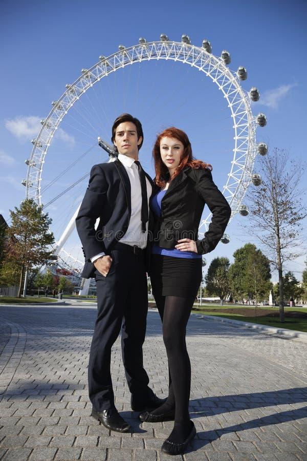 Retrato de los pares jovenes confiados del negocio que se unen contra el ojo de Londres, Londres, Reino Unido imagen de archivo libre de regalías