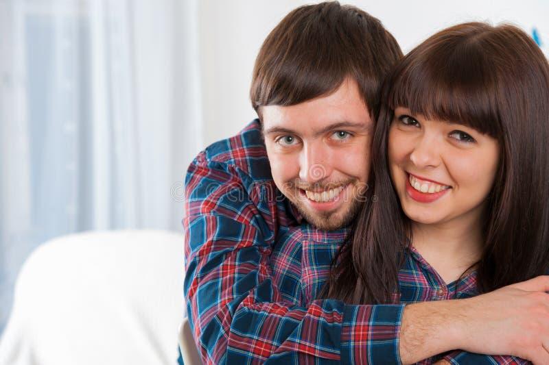 Retrato de los pares jovenes del amor que se sientan en el sofá y la sonrisa imagen de archivo