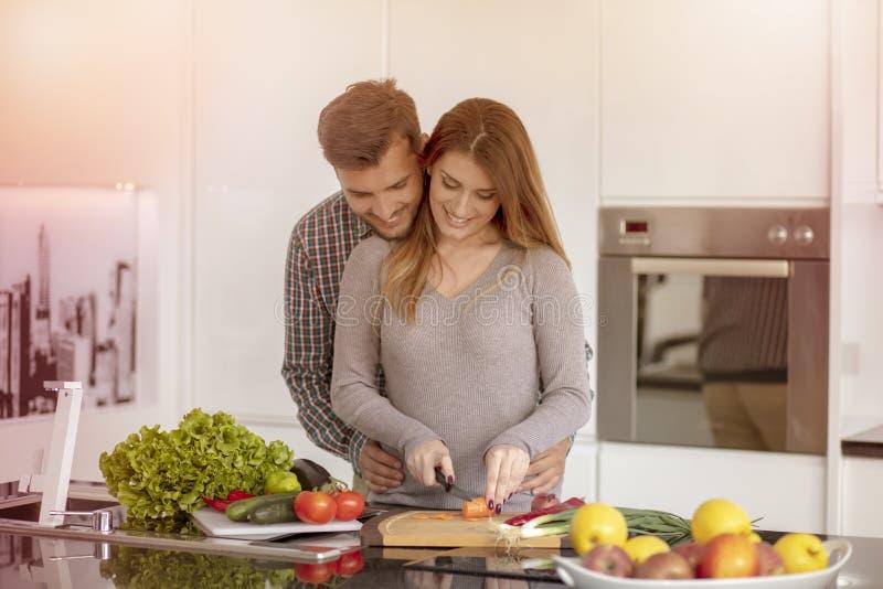 Retrato de los pares jovenes felices que cocinan junto en la cocina en casa fotos de archivo libres de regalías