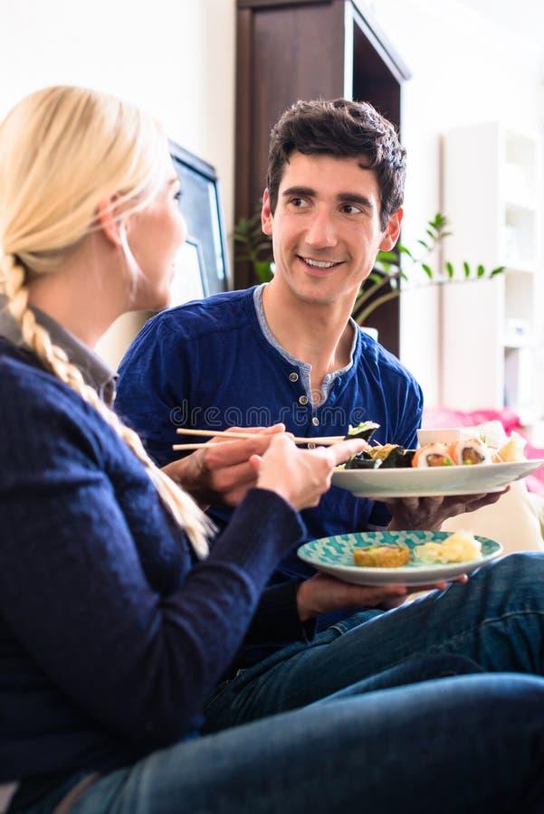 Retrato de los pares jovenes felices que comen la comida asiática tradicional imágenes de archivo libres de regalías
