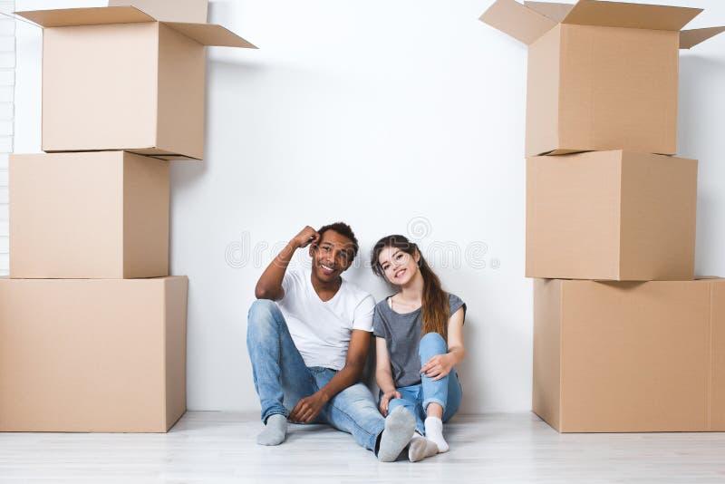 Retrato de los pares jovenes felices que se sientan en el piso que mira la cámara y que sueña su nuevos hogar y equipamiento imagen de archivo libre de regalías