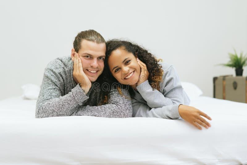 Retrato de los pares jovenes de la raza mixta emocionada feliz que mienten en cama su sonrisa junto y que miran la cámara en casa fotos de archivo