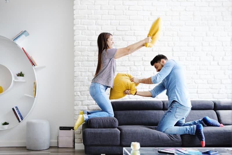 Retrato de los pares jovenes que juegan lucha de almohada imagen de archivo libre de regalías
