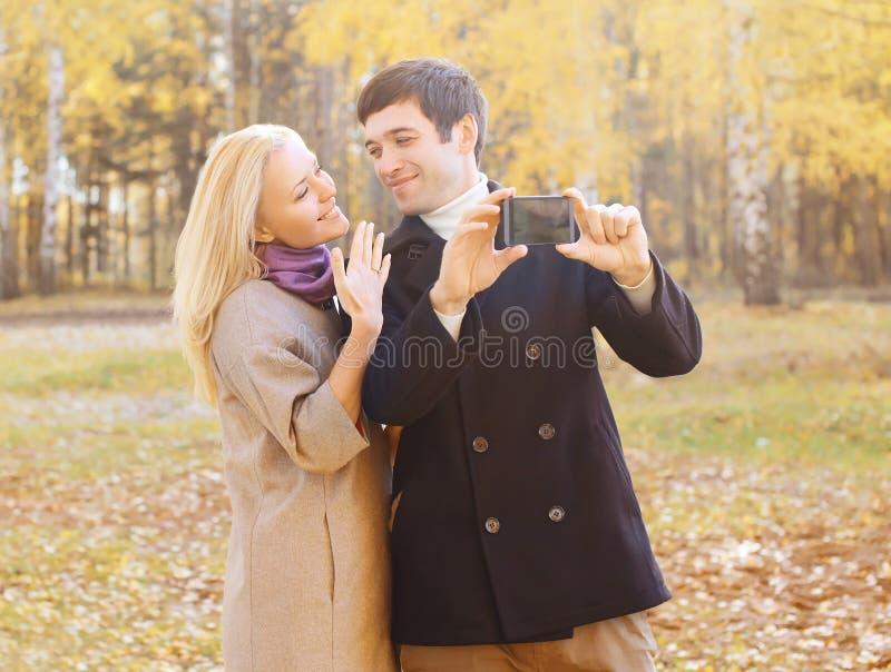 Retrato de los pares jovenes sonrientes felices que hacen el selfie en smarphone imagen de archivo
