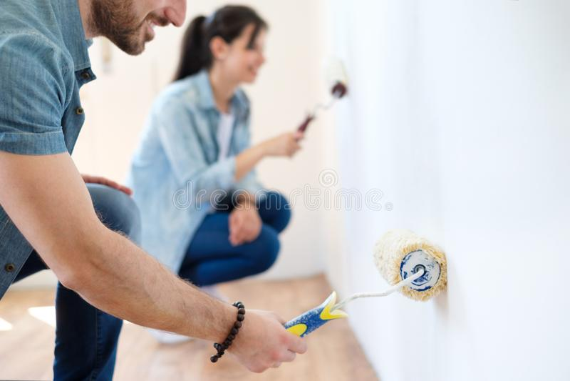 Retrato de los pares jovenes sonrientes que pintan la pared interior de nueva a fotografía de archivo