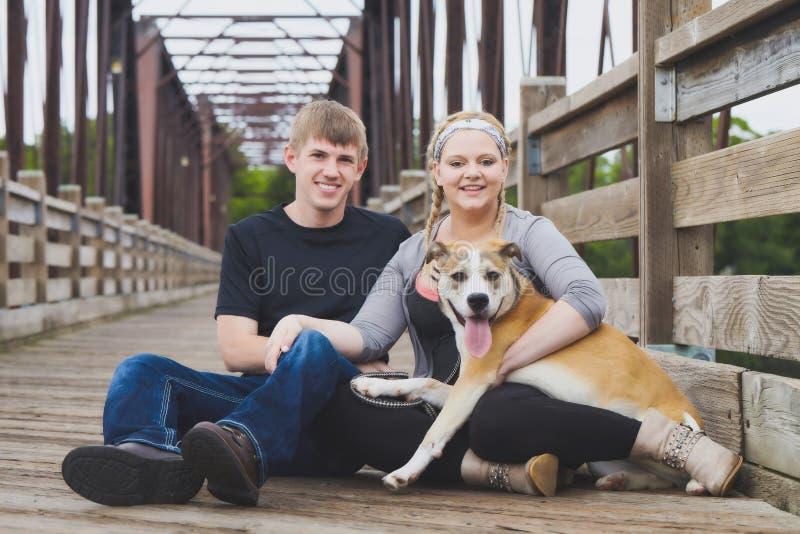 Retrato de los pares jovenes sonrientes que se sientan con el perro fotografía de archivo libre de regalías