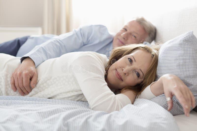 Retrato de los pares maduros que se relajan en cama en casa fotos de archivo libres de regalías
