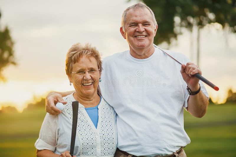 Retrato de los pares mayores felices que disfrutan de la forma de vida activa que juega a golf fotografía de archivo