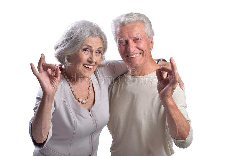 Retrato de los pares mayores felices que muestran muy bien en el fondo blanco fotografía de archivo