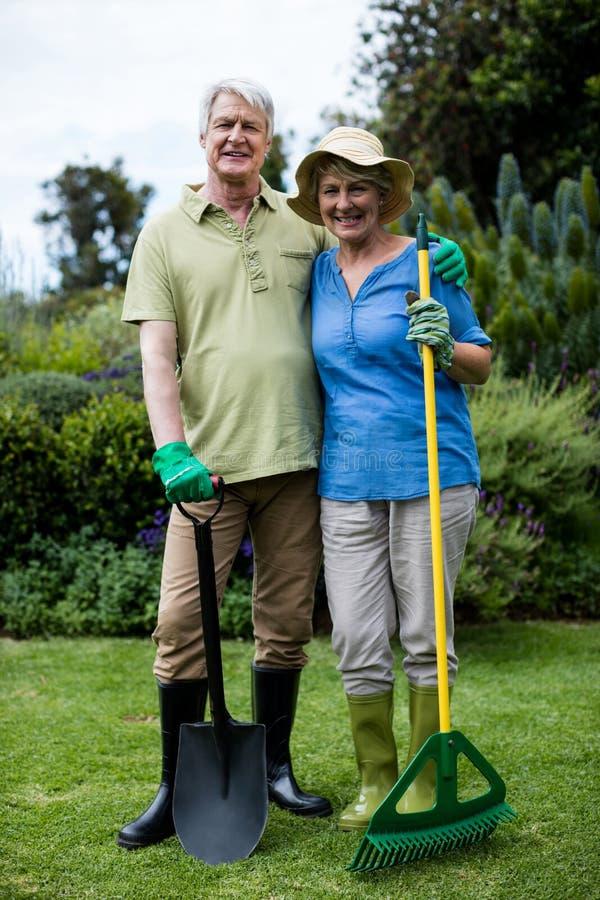 Retrato de los pares mayores que se colocan con los utensilios de jardinería foto de archivo libre de regalías