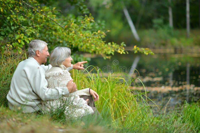 Retrato de los pares mayores que se sientan cerca del lago en oto?o imagen de archivo